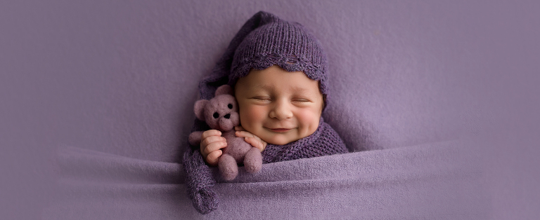 smiles newborn baby girl purple bear